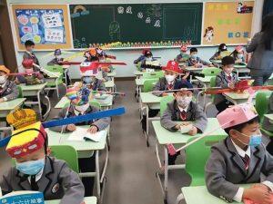 Cina, i bambini tornano a scuola con un cappello largo un metro per il distanziamento